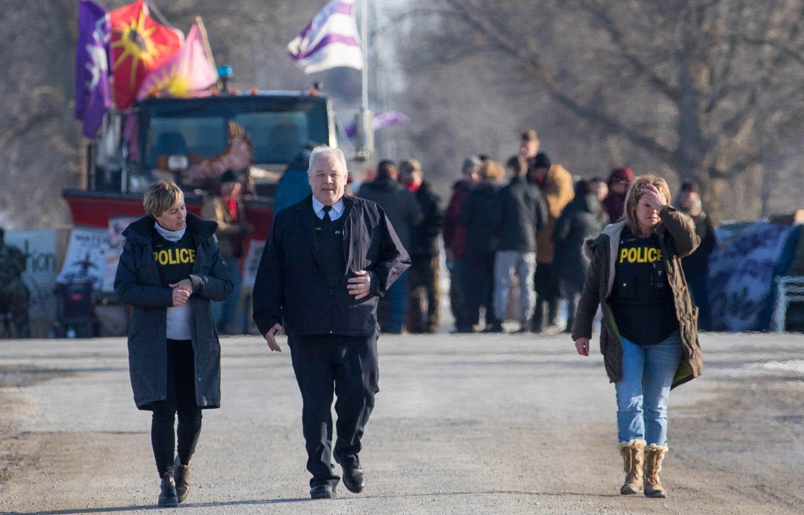 Des agents de la police provinciale de l'Ontario ont discuté avec des manifestants qui bloquent la voie ferrée à Tyendinaga, dimanche.