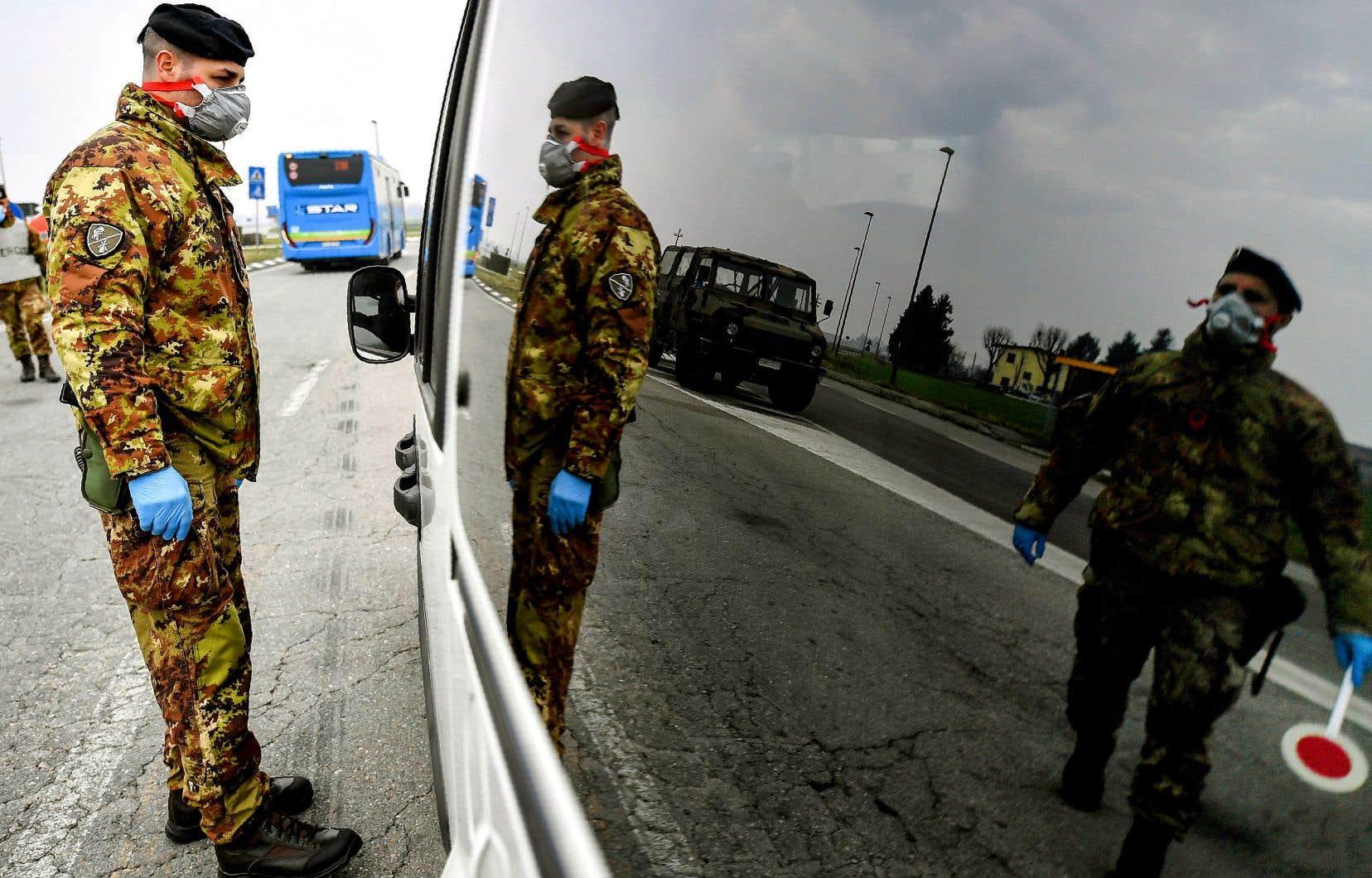 Des soldats de l'armée italienne portant un masque contrôlaient le transit routier à destination et en provenance de zones bouclées près de Turano Lodigiano, dans le nord de l'Italie, mardi. Près de 300 personnes auraient à ce jour été contaminées, selon un bilan récent.