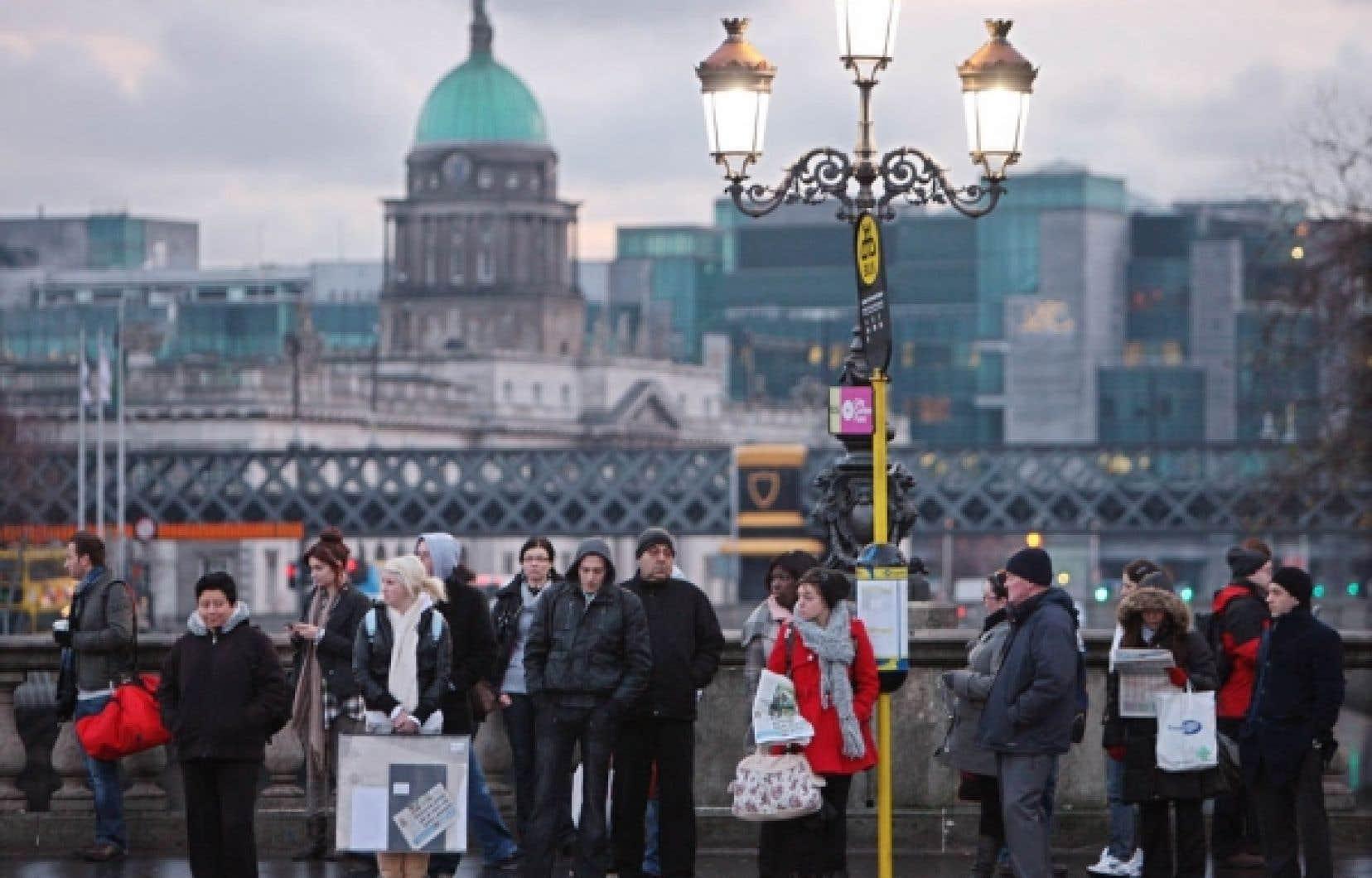 Des Irlandais attendent l'autobus dans une rue de Dublin. Des milliers d'entre eux devraient manifester aujourd'hui leur opposition au plan de rigueur, préalable au secours de la Banque centrale européenne et du Fonds monétaire international.<br />