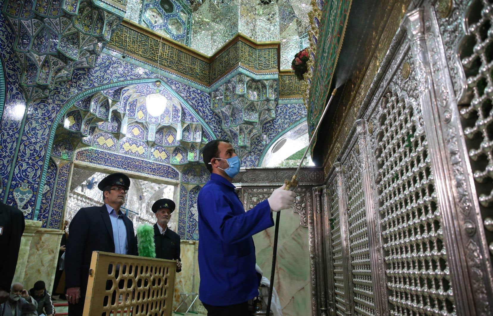 Un homme s'affaire à désinfecter le mausolée de Qom.