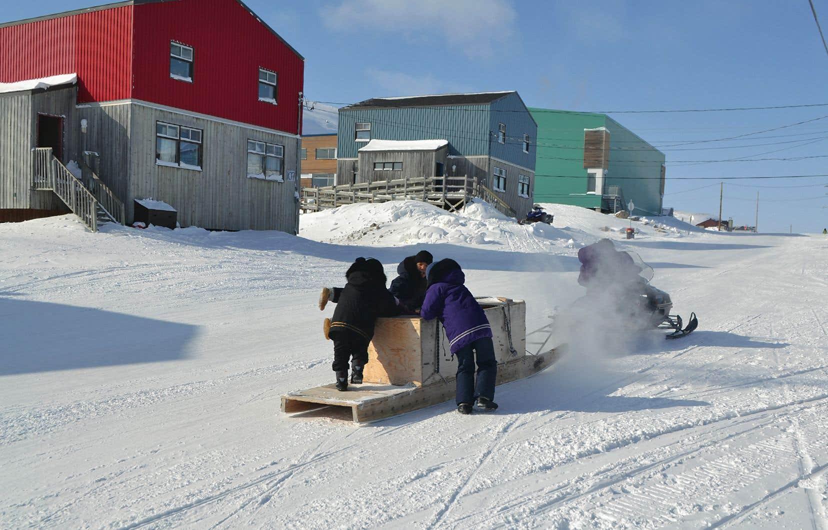 Des enfants dans un traîneau tiré par une motoneige à Kangiqsualujjuaq
