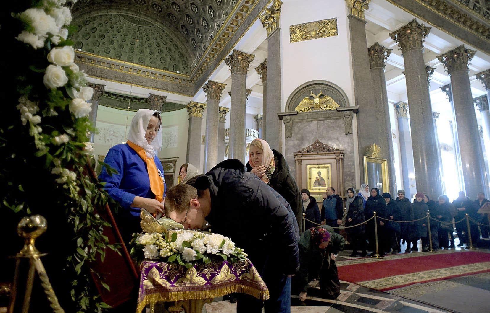 <p>Comme le veut la religion orthodoxe russe, les pratiquants se signent devant les objets saints et embrassent la vitre qui les recouvre.</p>