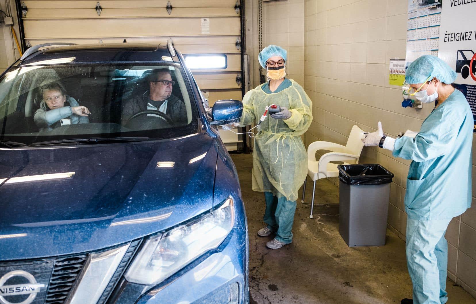 Des infirmières prennentun échantillon dans la bouche d'homme et son épouse qui reviennent d'un séjour au Costa Rica.