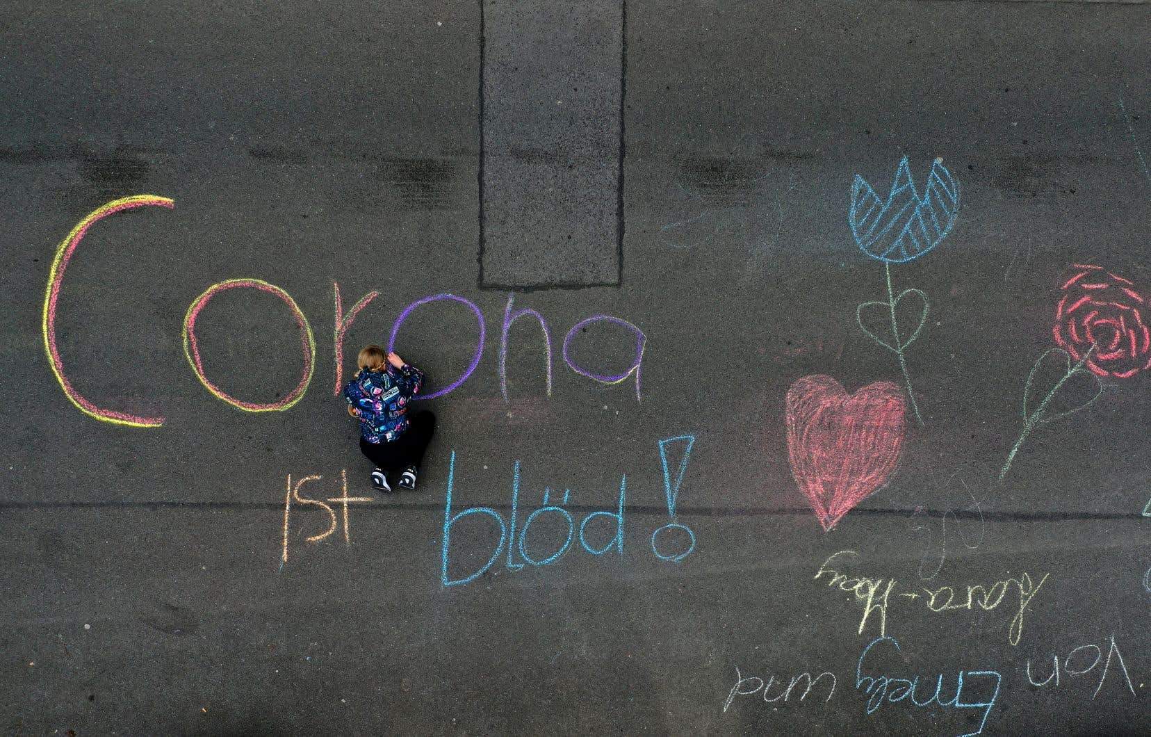 Emely, 10 ans, écrivait à la craie «Le corona, c'est poche», jeudi à Dortmund, dans l'ouest du pays.