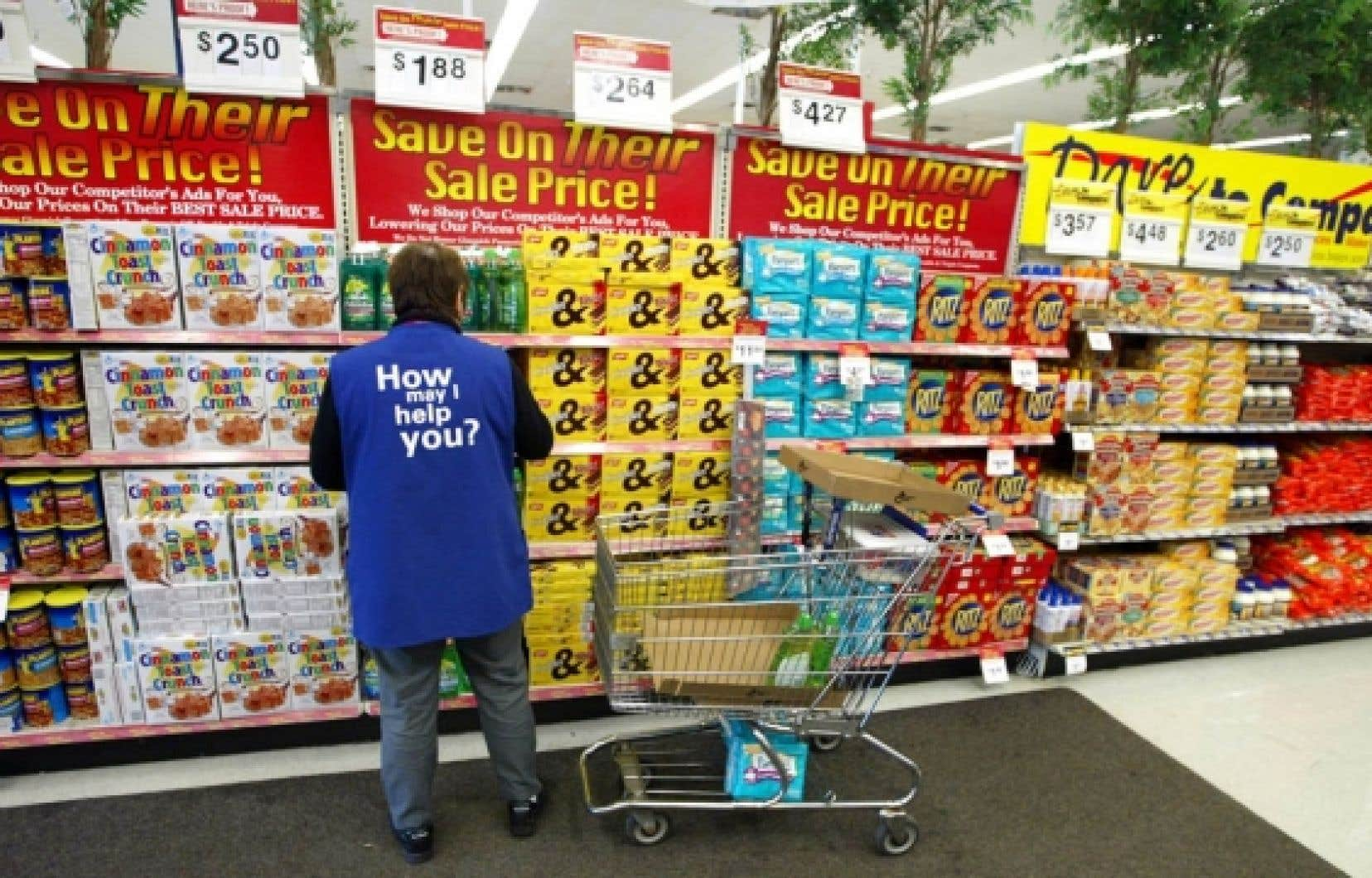 Une employée de Wal-Mart place de la marchandise sur les tablettes d'un commerce.<br />