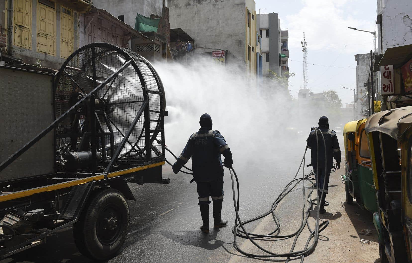 Des pompiers indiens répandent du désinfectant dans les rues.