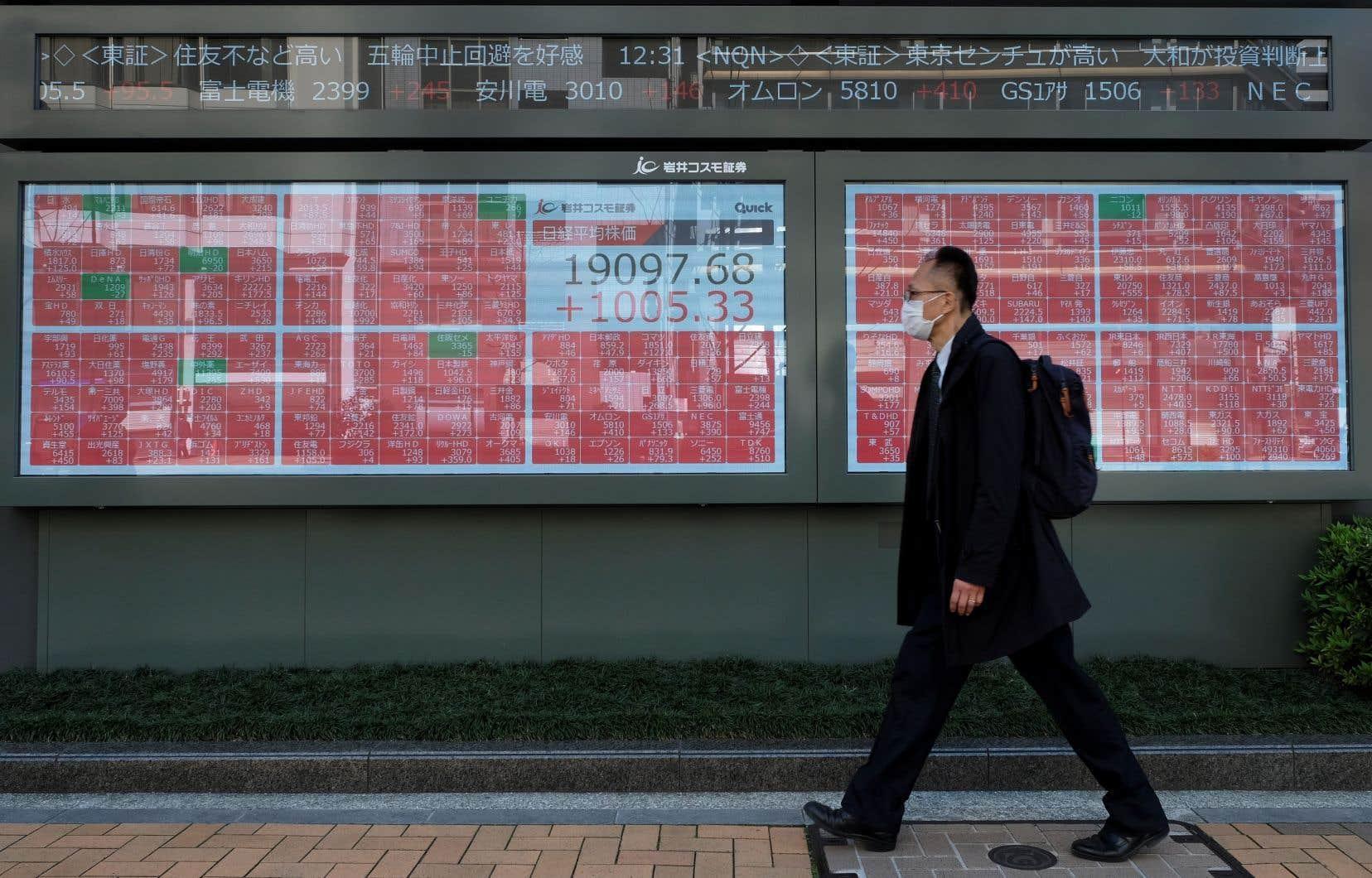 Un homme passant devant des tableaux qui affichent les fluctuations de la Bourse de Tokyo, dont la séance de mercredi s'est terminée sur la plus forte hausse depuis 2008 dans la foulée de l'accord de relance aux États-Unis.