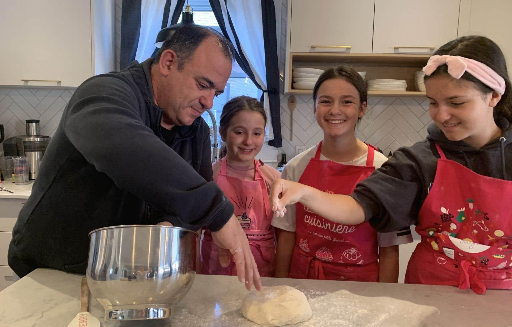 Éric Gauthier prépare  une pâte  à pain avec  ses trois filles.