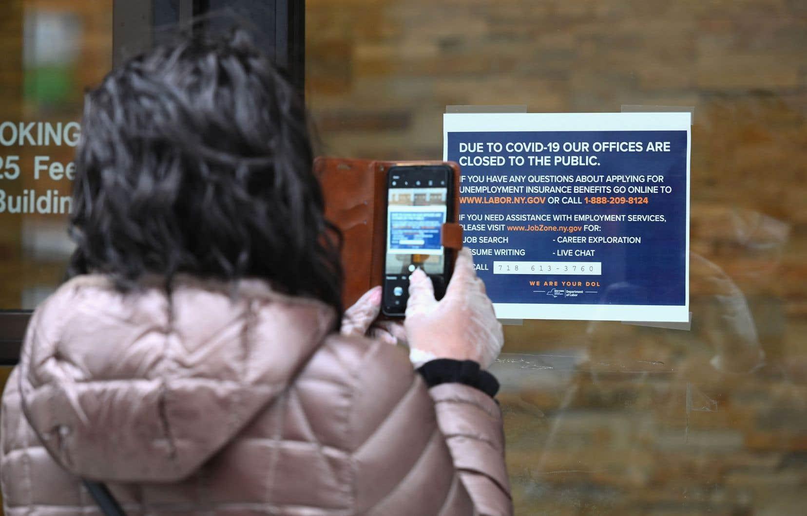 Une femme prend en photo les directives pour obtenir de l'assurance-chômage, devant les bureaux fermés du Ministère du travail, à New York.