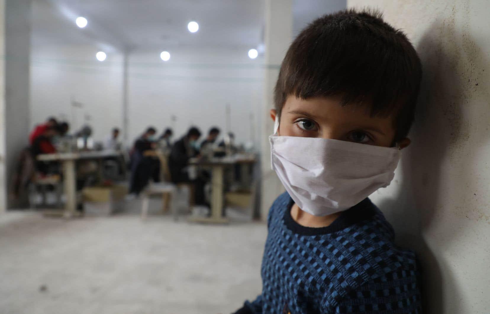 À Idlib, dans le nord-ouest de la Syrie, des bénévoles cousaient la semaine dernière dans un atelier des masques de protection comme celui que porte cet enfant.