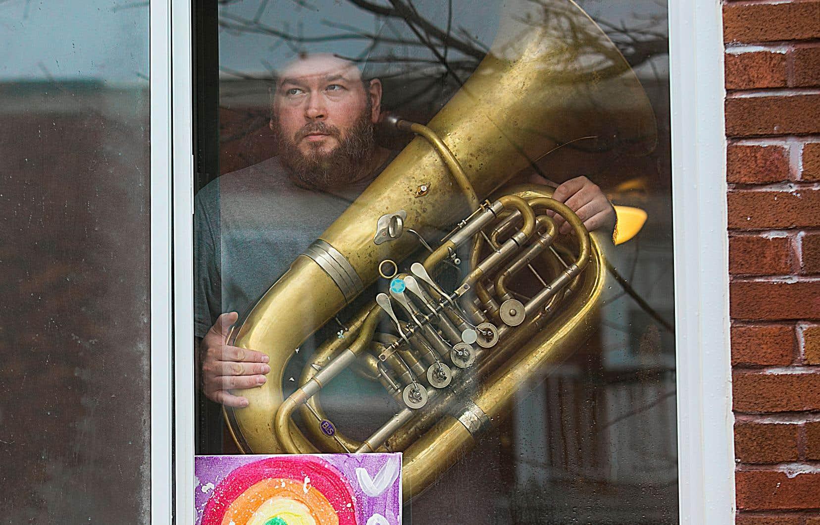 Christian Leclerc, tuba en main, pose devant les dessins d'arcs-en-ciel affichés par ses enfants.
