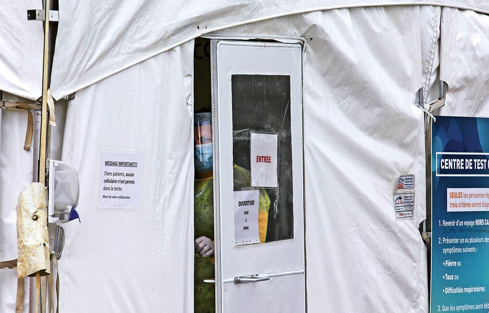 Une infirmière entrouvre la porte d'un centre de test temporaire installé à l'hôpital de Granby.