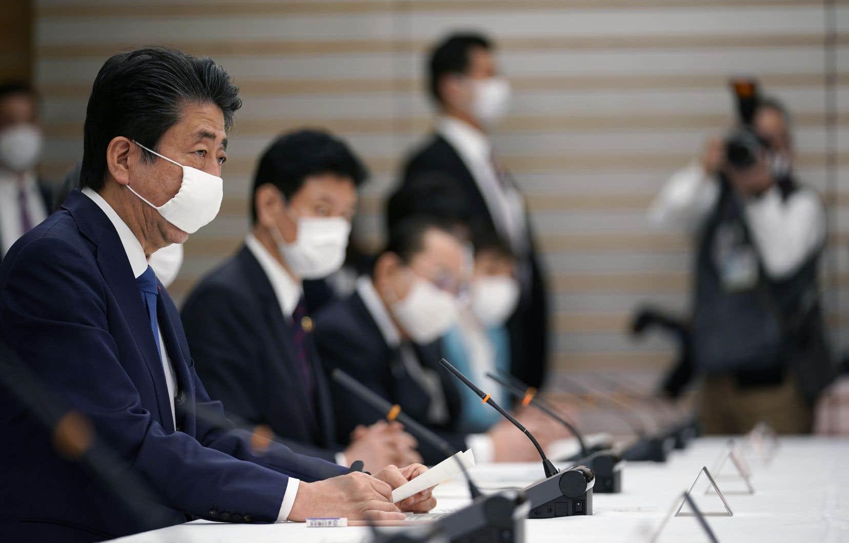 Le premier ministre japonais Shinzo Abe (à gauche) prend la parole lors d'une réunion au siège pour des mesures contre la nouvelle maladie à coronavirus, à Tokyo, le 6 avril 2020.