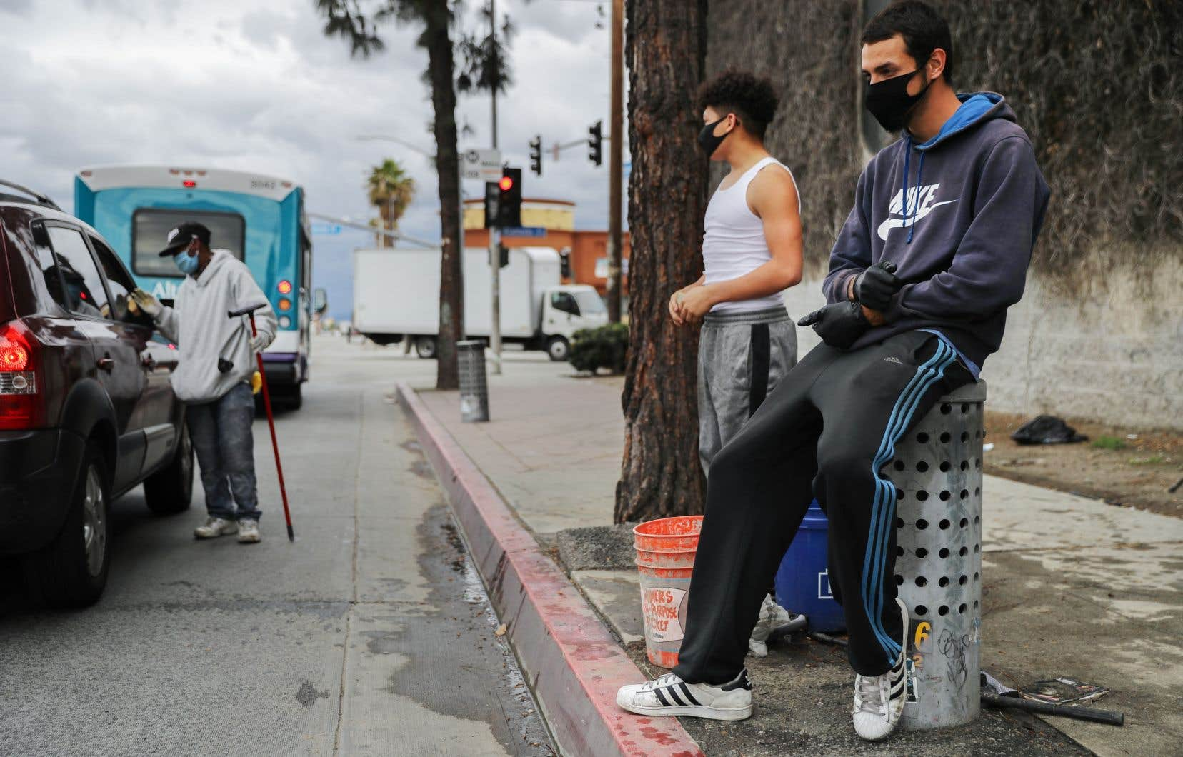 Des laveurs de pare-brises, protégés par un masque, attendaient des clients au coin d'une rue de Los Angeles, mardi.
