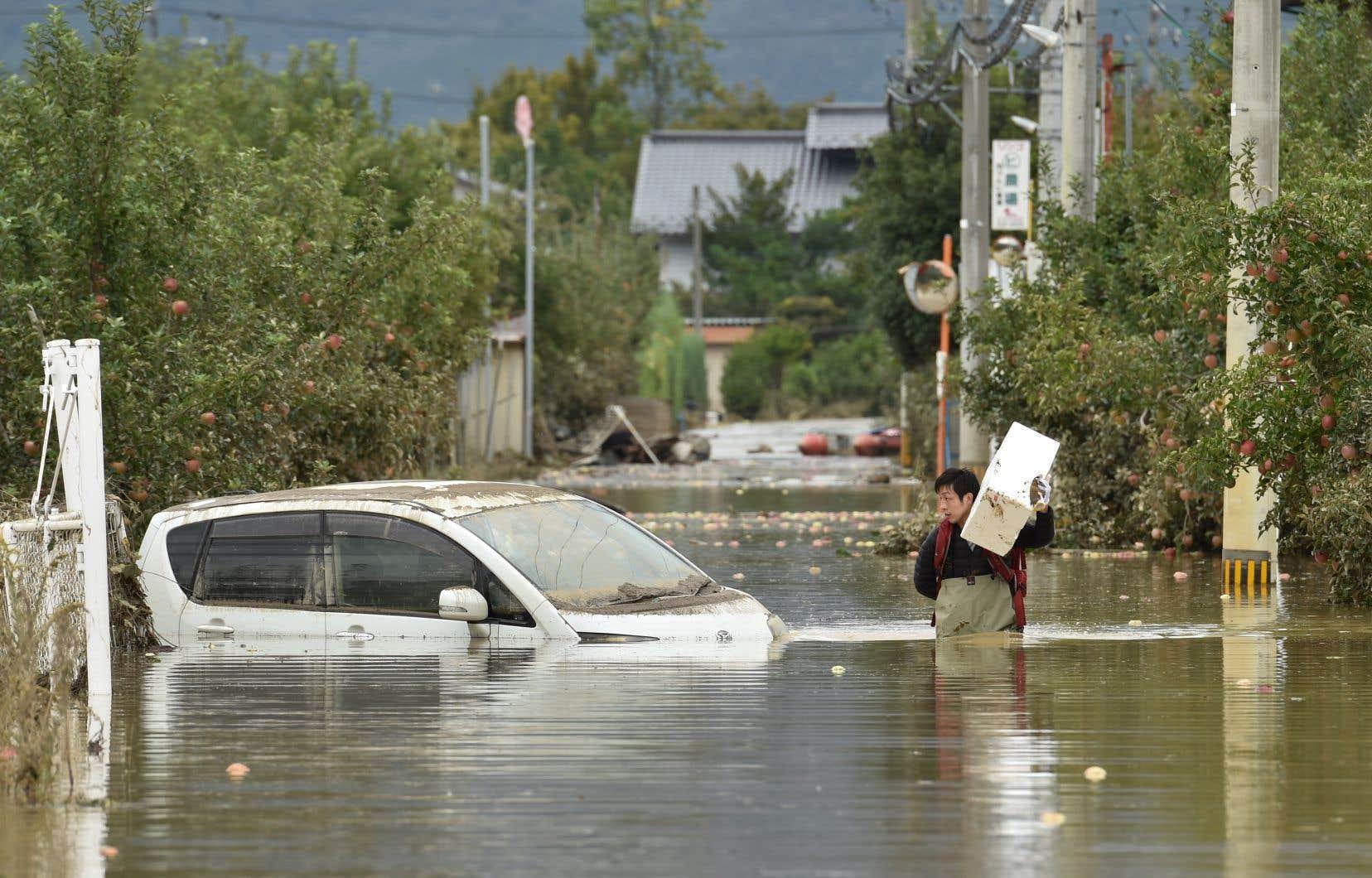 Le typhon «Hagibis», au Japon, a été l'un des phénomènes les plus couteux pour le secteur des catastrophes naturelles. Sur notre photo, un homme circule dans une rue inondée de Nagano, au Japon, après le passage du typhon en octobre dernier.