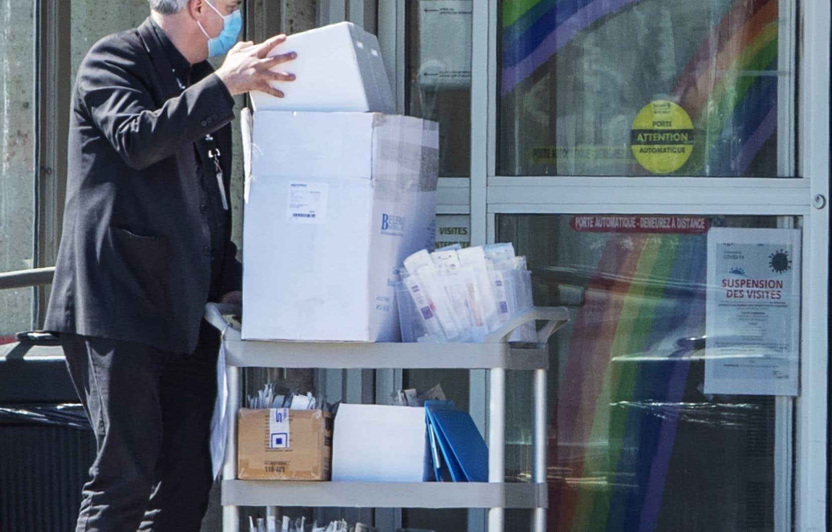 Un travailleur de la santé transporte du matériel au CHSLD Sainte-Dorothée, à Laval, durement éprouvé par la pandémie.