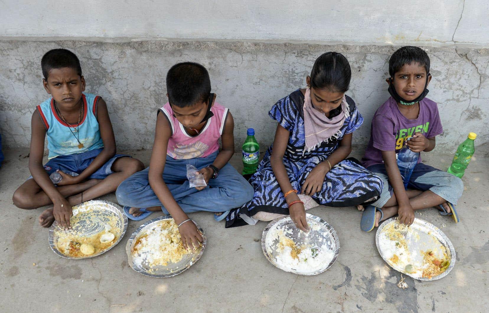 Des enfants mangent un repas distribué par une organisation caritative à Secunderabad, en Inde. Selon l'ONU, «368,5 millions d'enfants dans 143 pays dépendent normalement des repas scolaires comme source fiable de nutrition quotidienne».