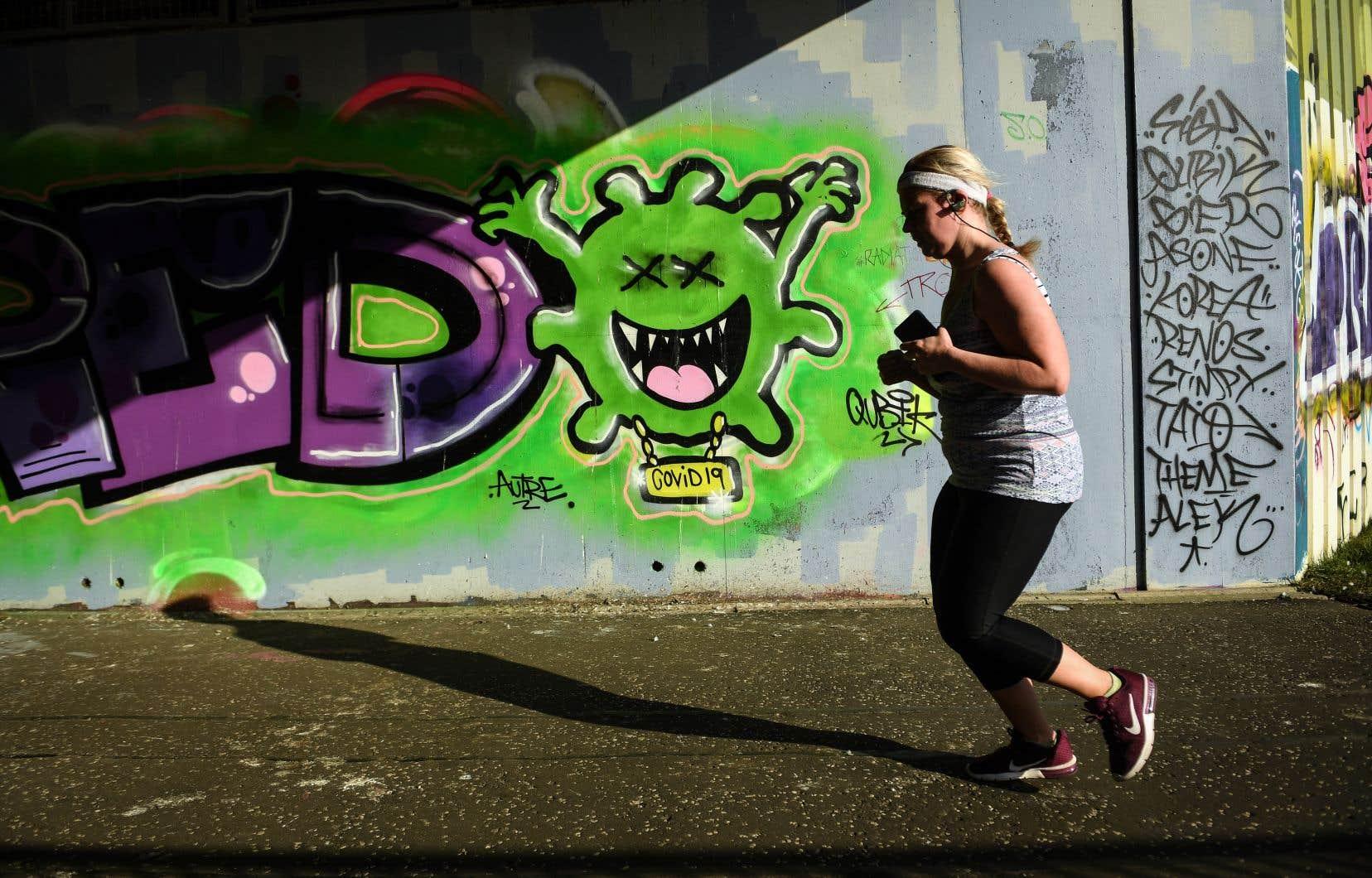 Une joggeuse passait devant un graffiti, samedi, à Glasgow. Mardi, le Parlement britannique devrait reprendre ses travaux, principalement en vidéo-conférence.