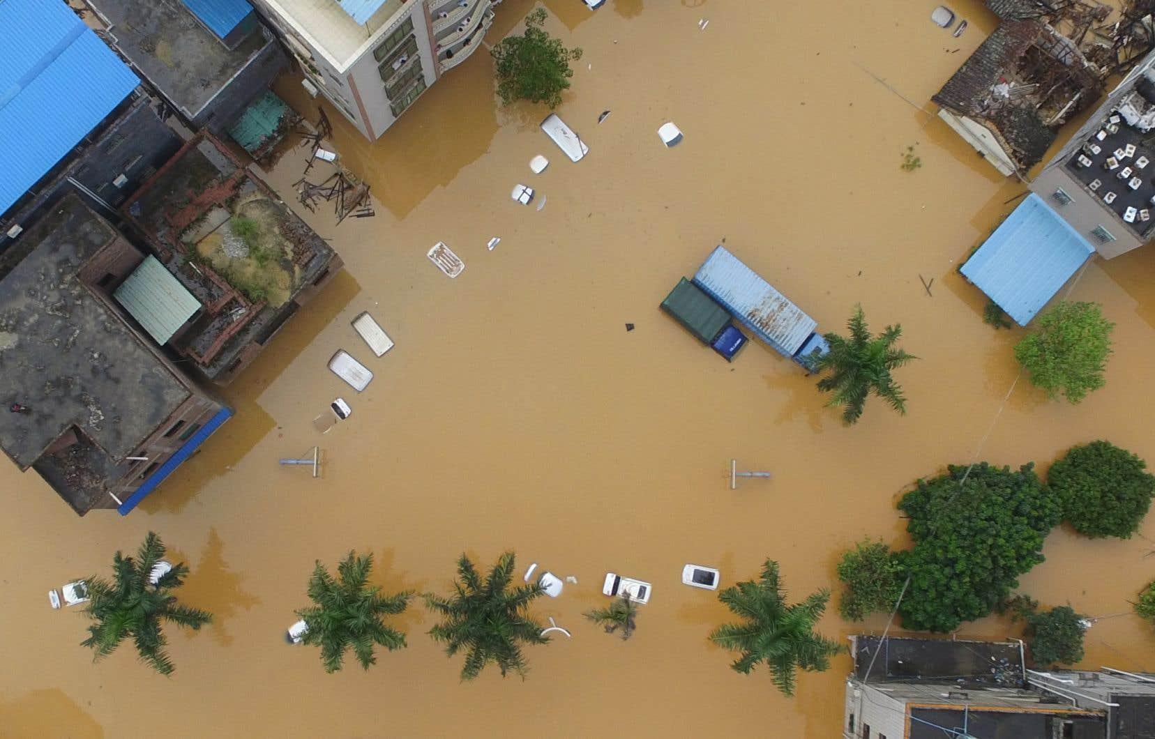 Pour le moment, la crise a surtout eu pour effet de repousser des rendez-vous cruciaux en matière de protection de l'environnement à laquelle sont liés les changements climatiques et leurs conséquences catastrophiques, comme ici  les inondations de 2017 dans  le quartier  de Zengcheng,  à Guangzhou, dans la province chinoise du Guangdong.