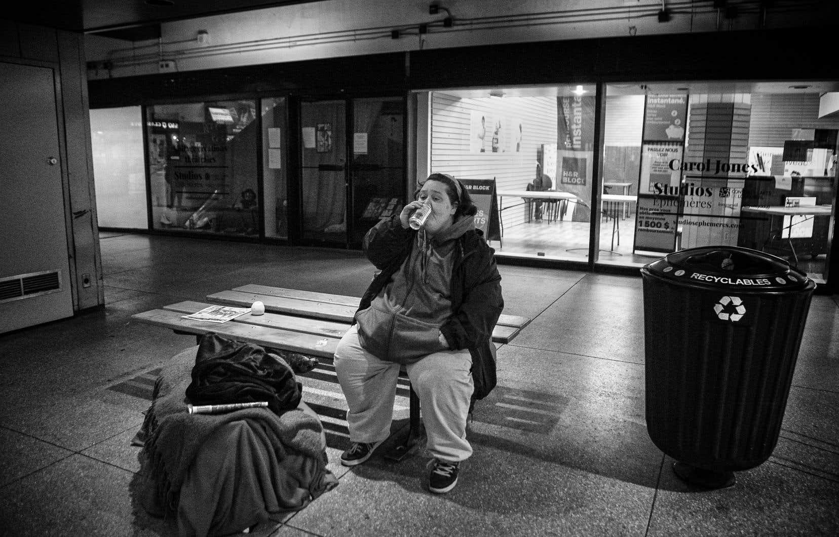 Lisa, une itinérante boit et mange un repas que les policiers ont apporté dans la station de métro de Longueuil en début d'après-midi, vendredi.