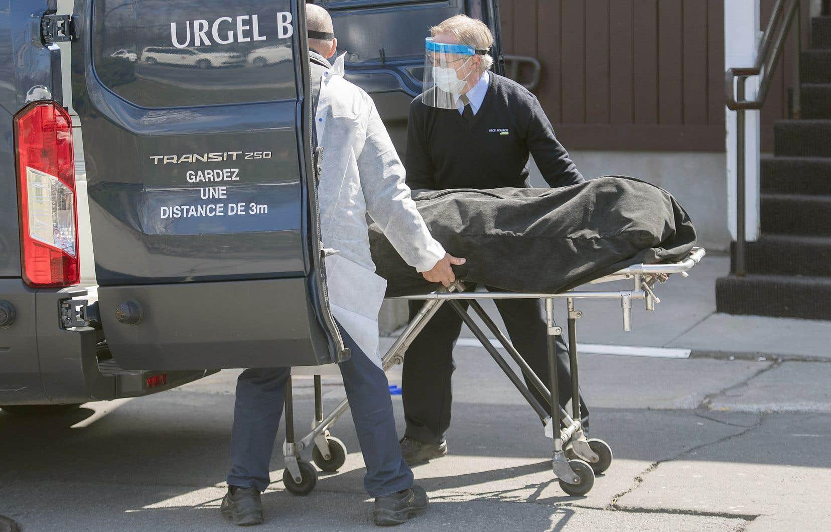 Des employés d'une entreprise funéraire s'occupent de la dépouille d'une personne décédée de la COVID-19 dans une résidence pour personnes âgées de Montréal.