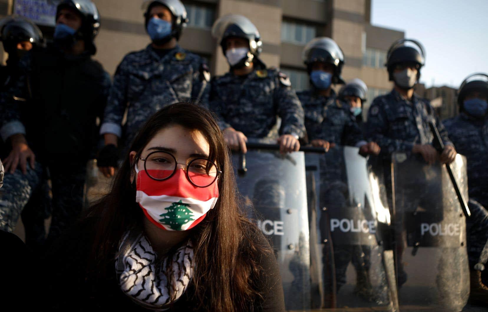 Une manifestante s'assoit en protestation devant les policiers antiémeute, mardi à Beyrouth.