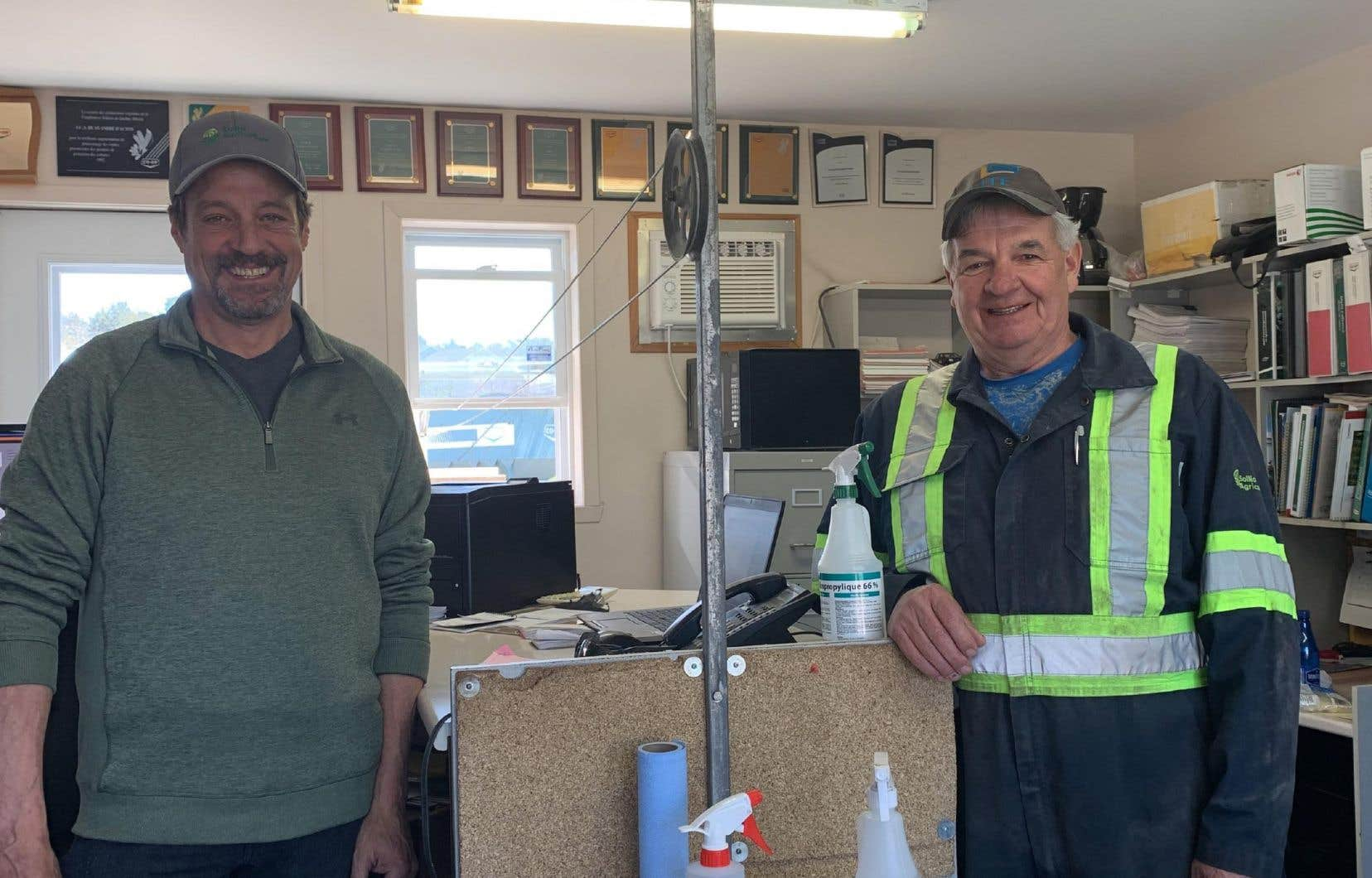 Pour éviter les contacts, le contremaître Denis Desroches (à gauche) a mis au point un système de corde à linge qui relie deux poteaux installés à l'intérieur et l'extérieur de  son bureau.