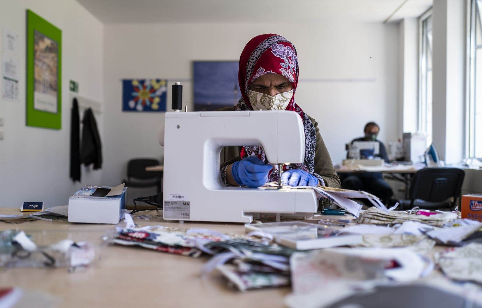 Une migrante d'origine afghane confectionne des masques dans un centre communautaire de Berlin.