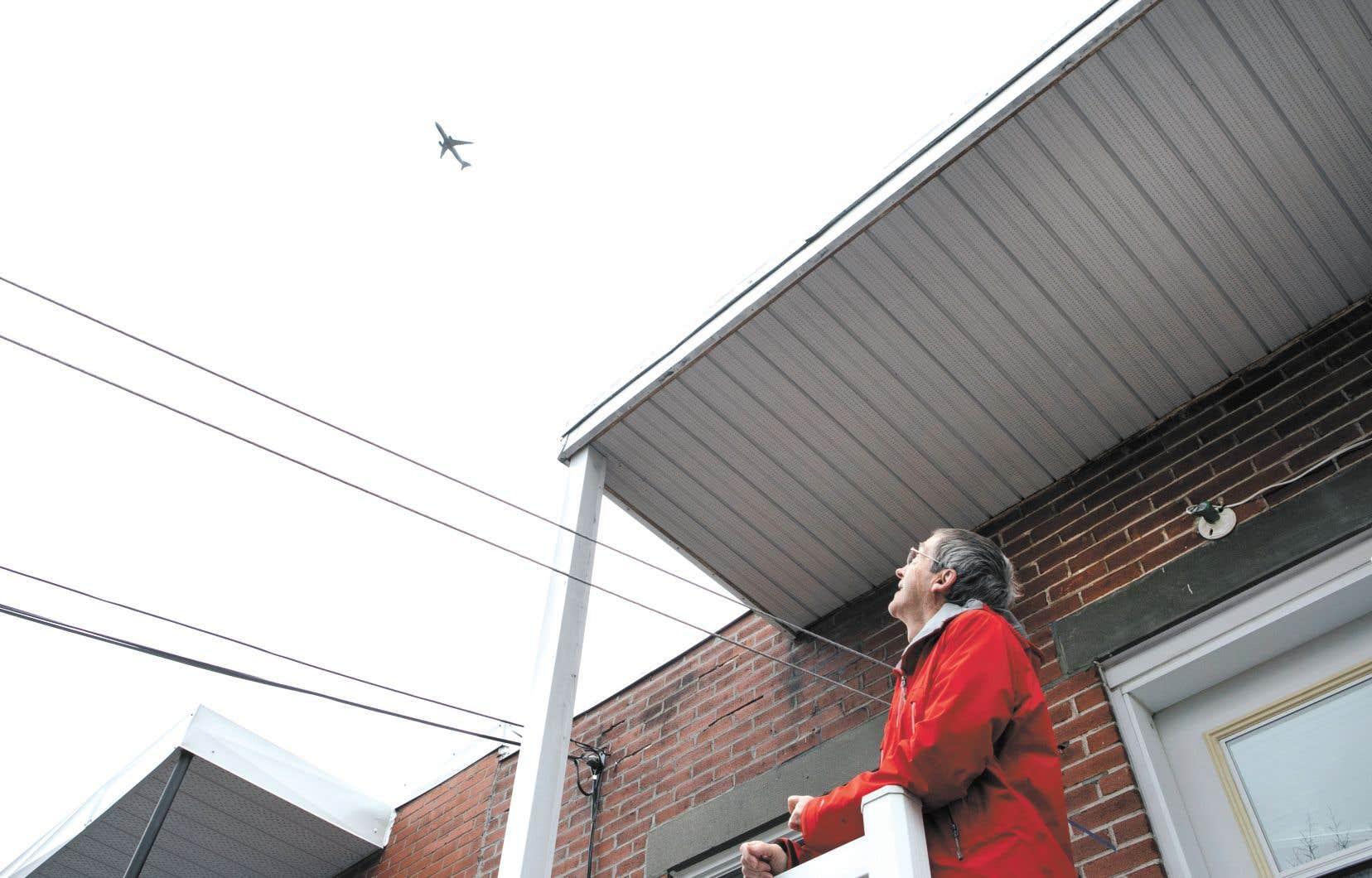 Pierre Lachapelle regarde à partir de son balcon un des rares avions qui décollent actuellement.