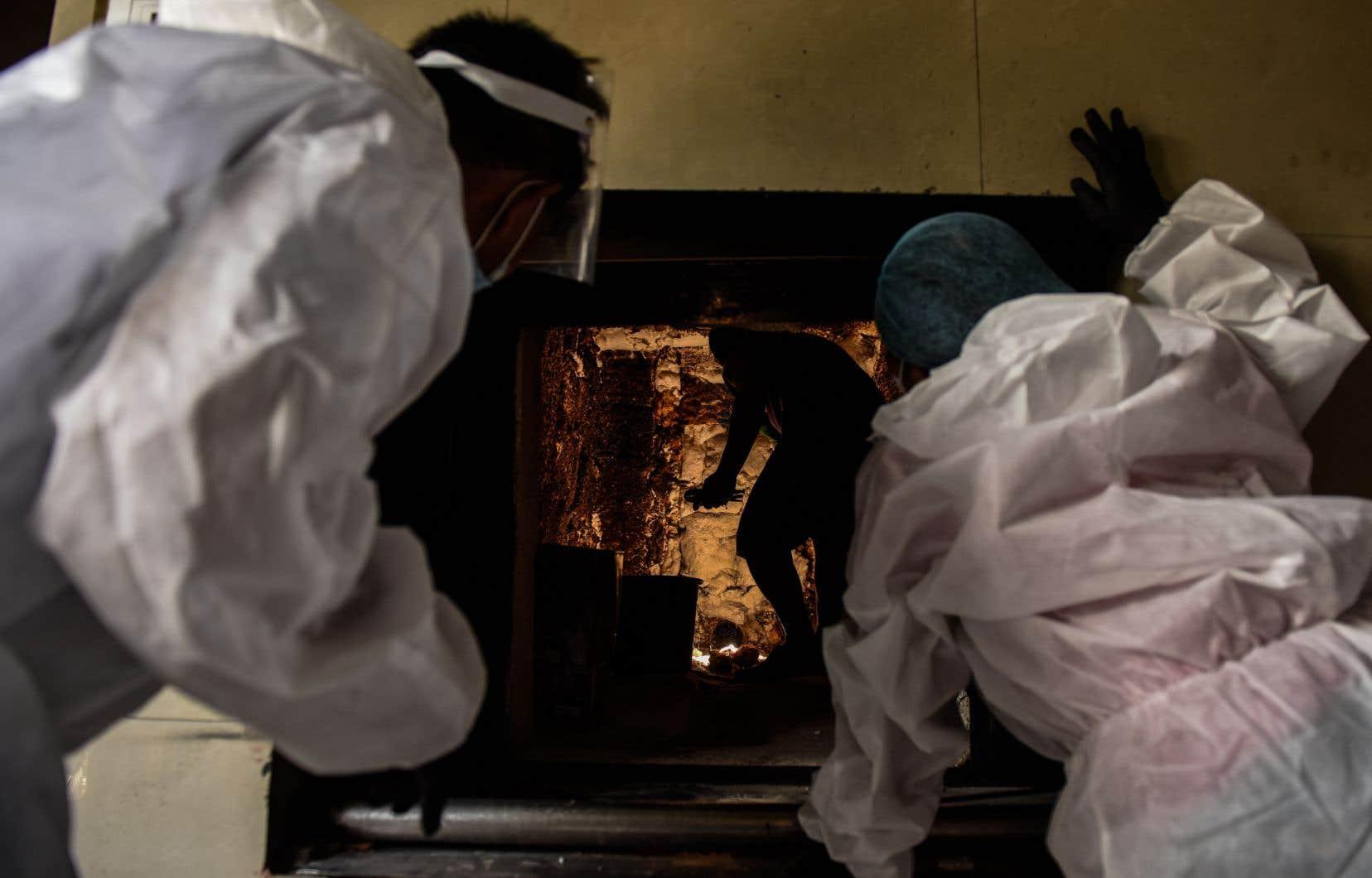 Un travailleur en blouse nettoie un four d'incinération sous les yeux de ses collègues. Aux Philippines, où les corps des défunts sont traditionnellement embaumés avant d'être exposés plusieurs jours, puis inhumés, les autorités encouragent désormais une crémation expéditive.