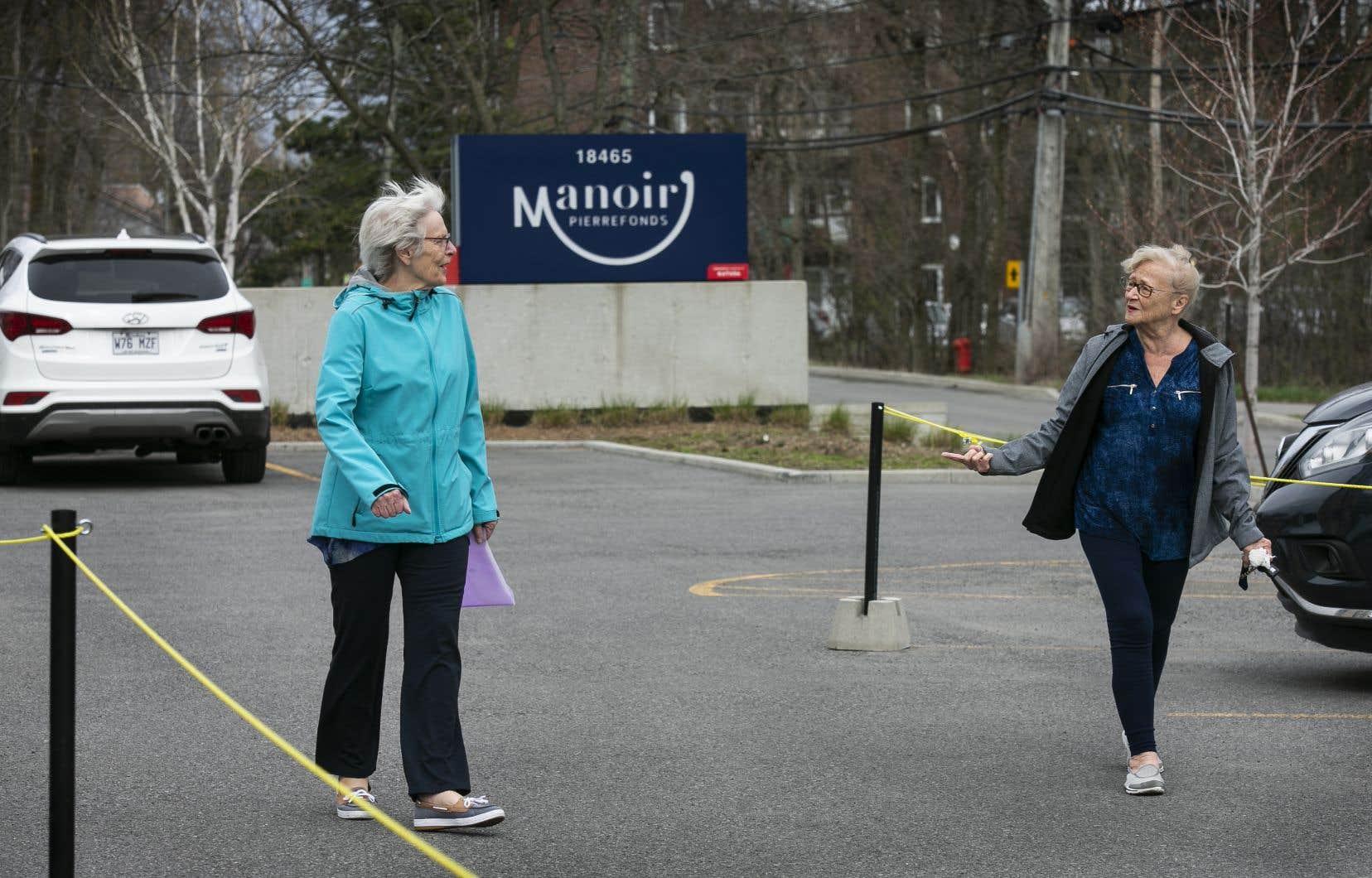 Jodie Johnson, à gauche et Lorna Roberts, à droite, font partie des quelques résidents du Manoir Pierrefonds qui peuvent suivre un parcours lors de leur petite marche à l'extérieur, dans le stationnement. Il n'y a pas de cas de COVID-19 dans cette résidence.