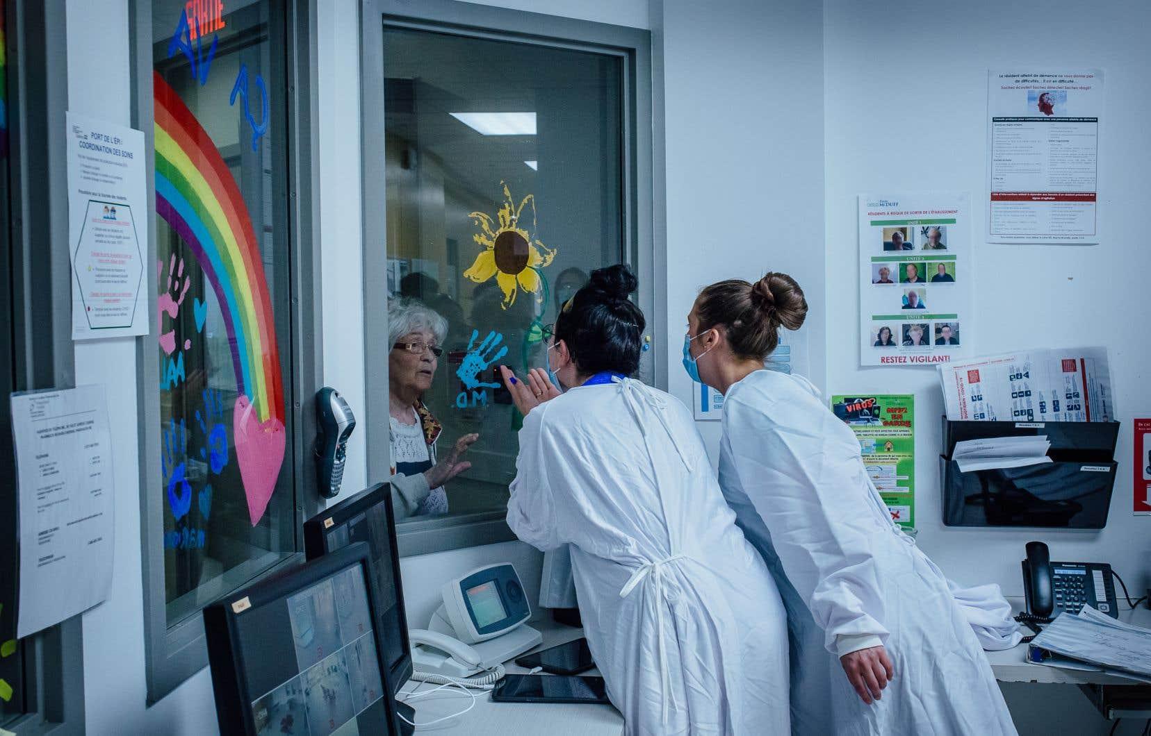 Une résidente atteinte de la COVID-19, surnommée «Mamy», essaie de quitter la zone rouge. Les infirmières Kim Gingras et Lara Gohier tentent de la rassurer.