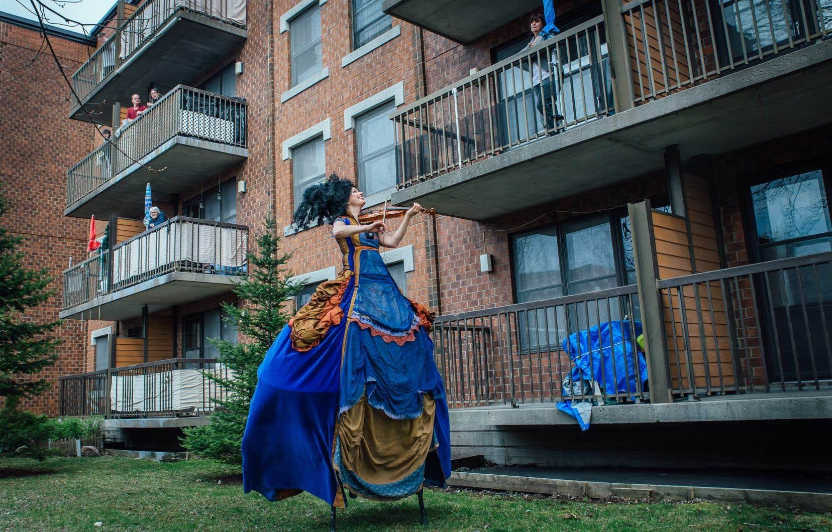 La troupe de théâtre de rue Drôldadon a lancé le projet Balconfinés: les artistes offrent une prestation de 30 minutes dans la cour des HLM de l'arrondissement Rosemont. Les résidents regardent de leur balcon.