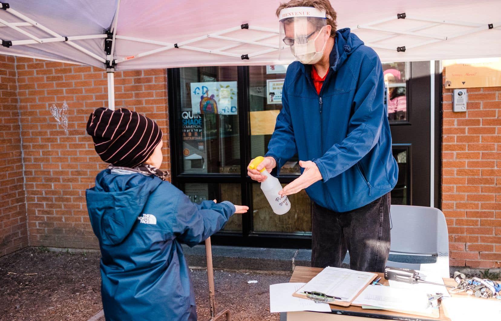 À l'école des Berges, à Québec, les enfants devaient passer par la station de désinfection des mains avant d'entrer dans l'école.
