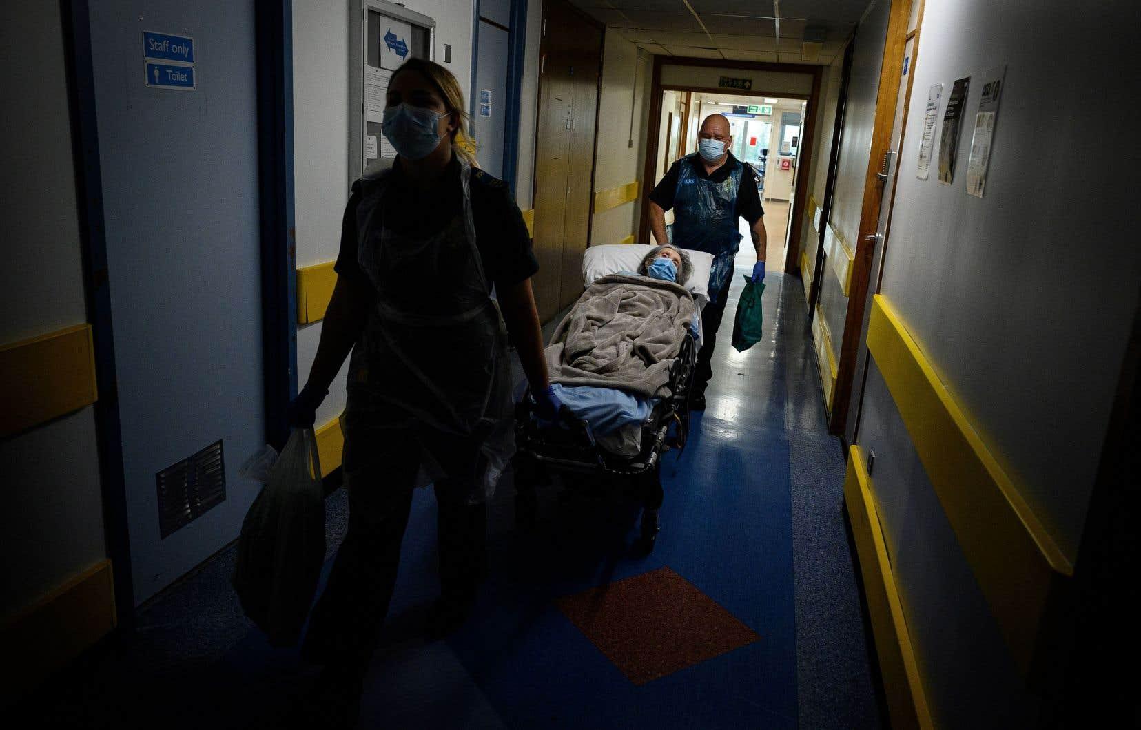 Les ambulanciers Katie Ffolloitt-Powell et Mike Carr déplacent une patiente âgée de l'hôpital vers une résidence près de Portsmouth, dans le sud-ouest de l'Angleterre.