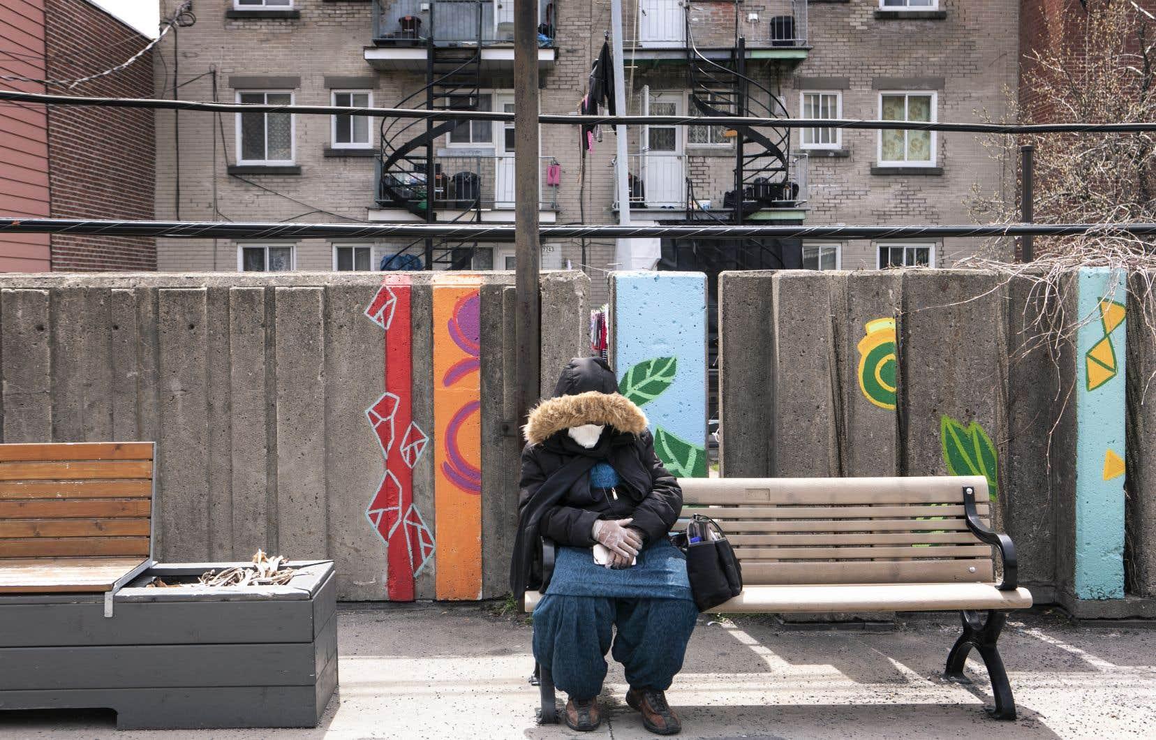 Une femme assise sur un banc a revêtu des gants et un masque, dans Parc-Extension.