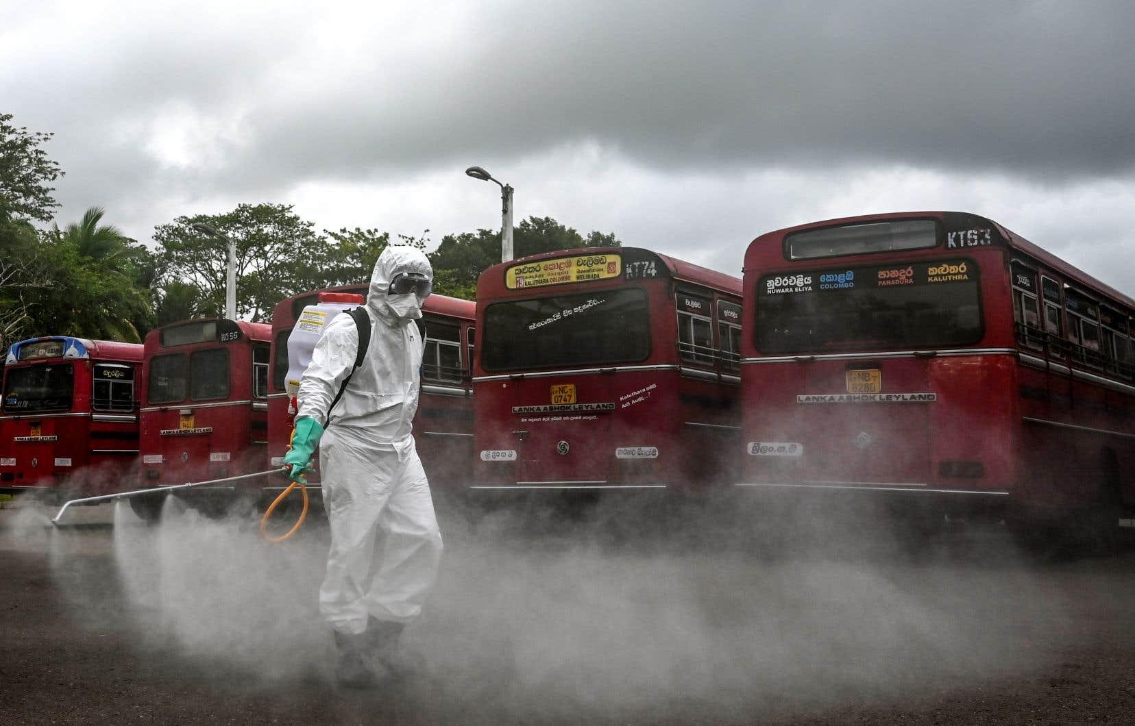 Un policier vêtu d'équipement de protection répand du désinfectant, au Sri Lanka. L'Organisation mondiale de la santé a prévenu samedi que cette pratique n'est pas efficace.