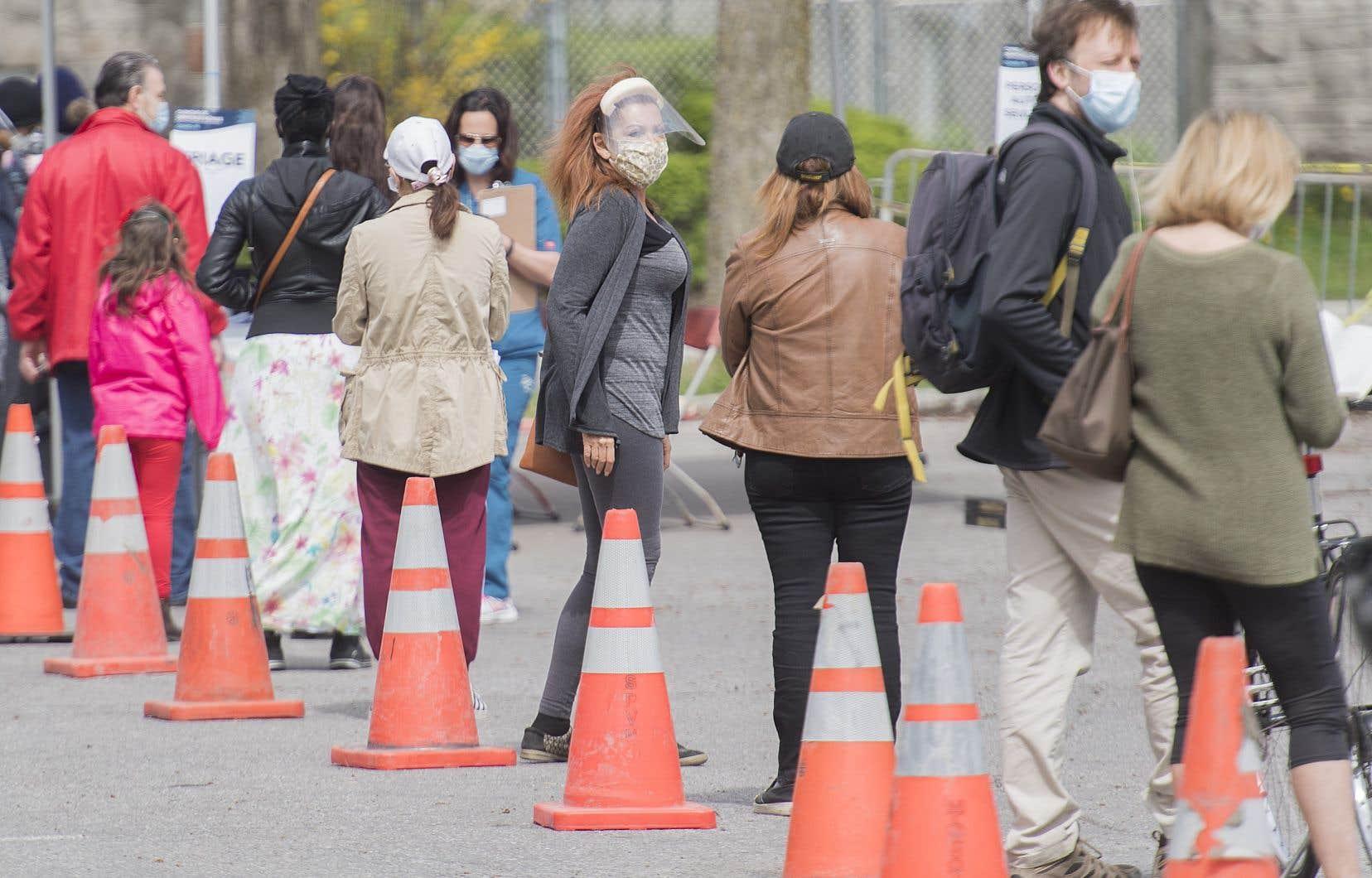 Des gens faisant la file afin d'être testés pour la COVID-19 dans une clinique mobile à Montréal, le dimanche 17 mai 2020