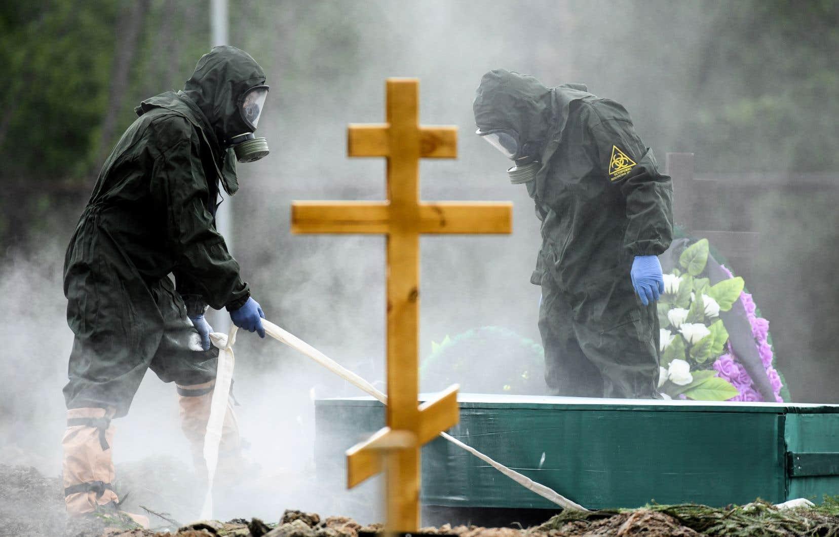 Des travailleurs sanitaires désinfectaient un cimetière vendredi près de Moscou. La Russie, le deuxième pays en nombre de cas détectés, se targue de sa faible mortalité liée au coronavirus, mais, dans la région du Caucase, les autorités sonnent l'alerte.