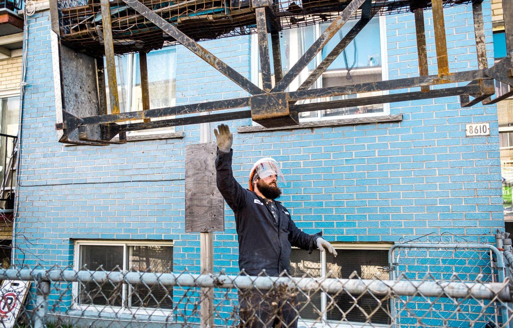 Certains secteurs d'activité, comme la construction résidentielle, pourraient connaître une relance plus  rapide. Sur la photo, un travailleur de la construction équipé d'une visière à Montréal.