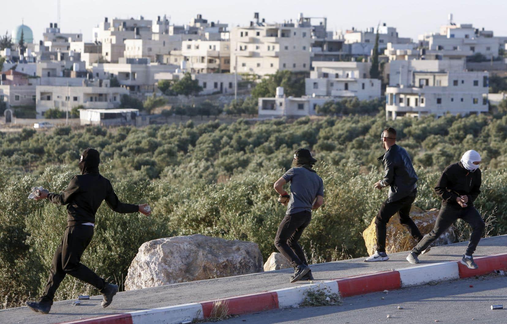 Des manifestants palestiniens lancent des pierres lors d'affrontements avec des soldats israéliens en Cisjordanie, jeudi.