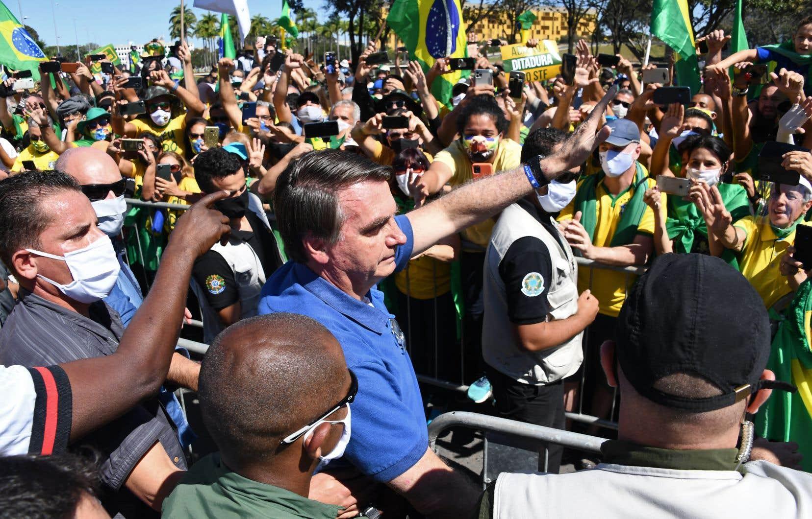 Le président brésilien a participé à un rassemblement avec ses partisans à Brasília, devant le palais présidentiel, bravant une nouvelle fois les normes sanitaires tout en se gardant cette fois de toucher les mains de la foule.