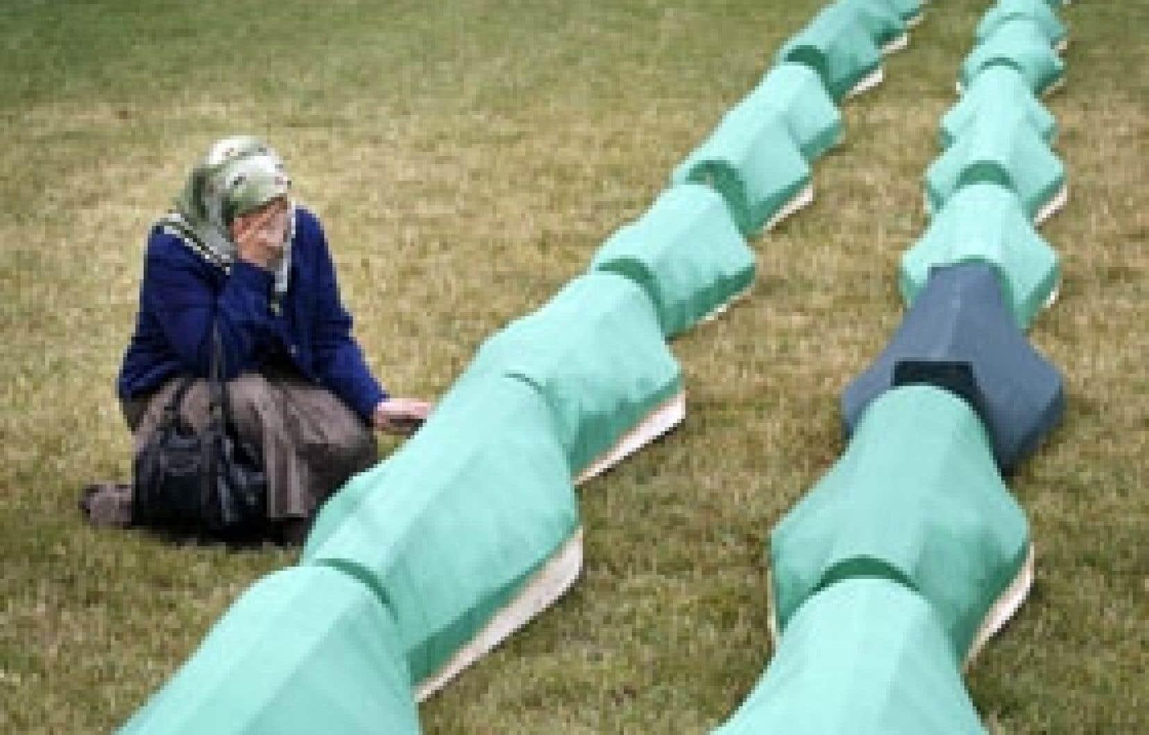 Une musulmane bosniaque priait cette semaine près de la tombe d'un proche, après une messe commémorative célébrée pour des victimes de la guerre en Bosnie.