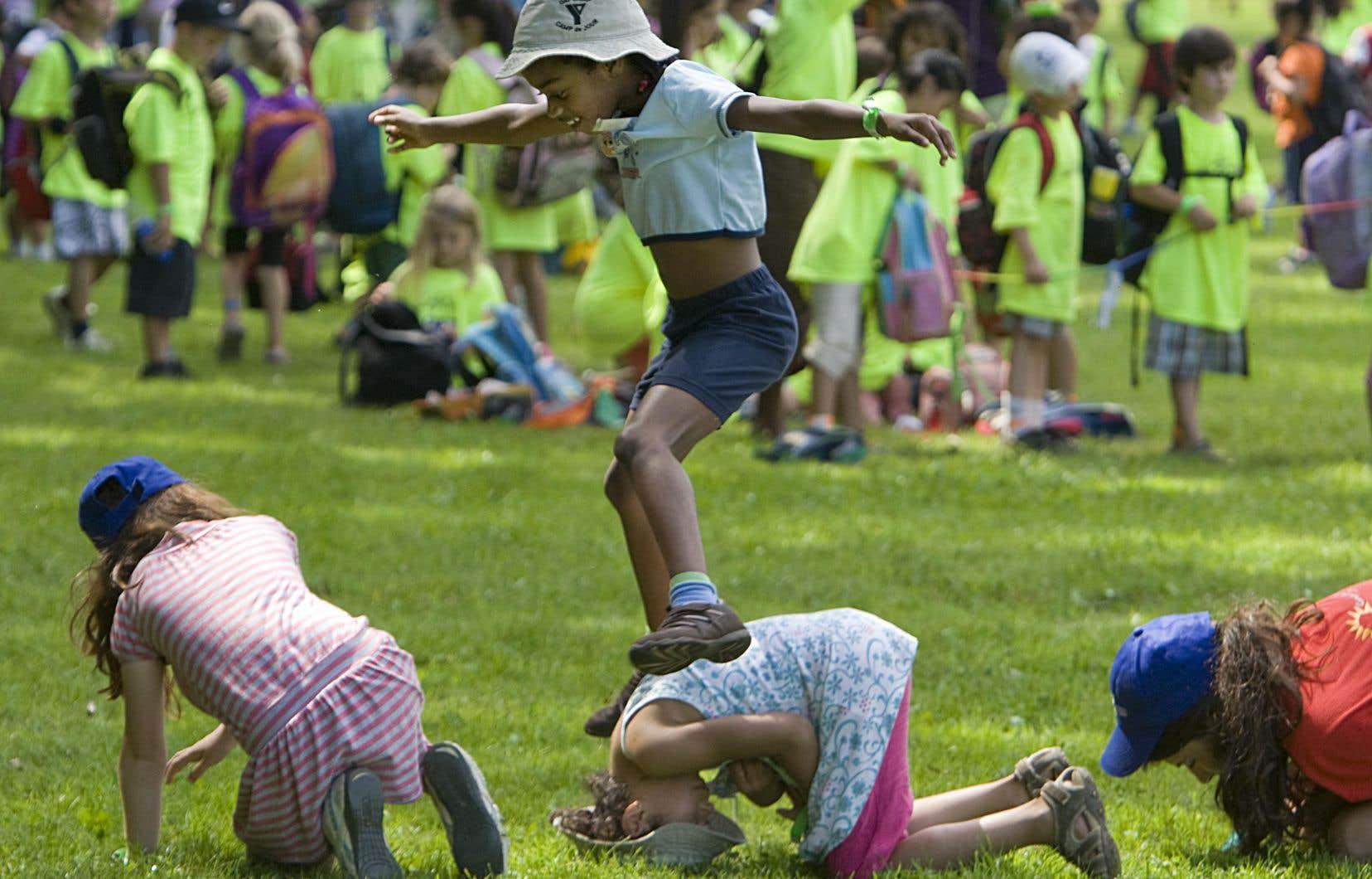 Sur cette photo prise en 2009, des enfants jouent à saute-moutons durant une activité de camp de jour. Ceux-ci pourront avoir autant d'enfants pour un moniteur qu'à l'habitude cet été, a décidé le gouvernement Legault mercredi.