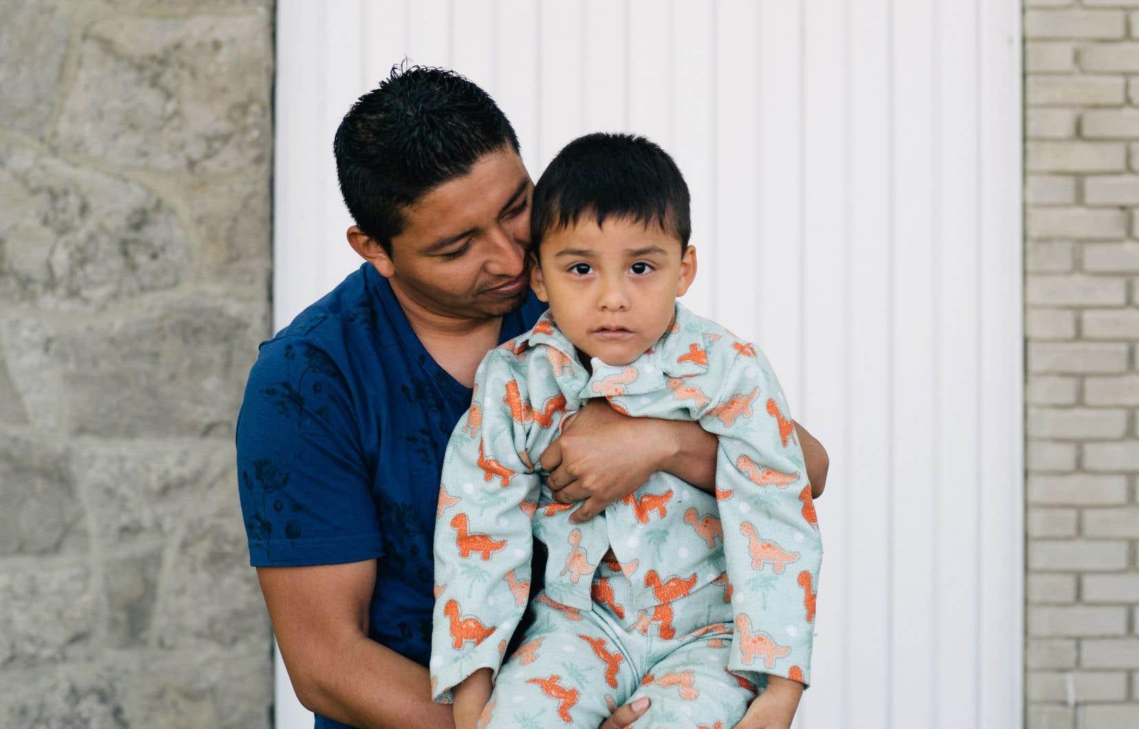 Devant un supermarché Métro, l'organisme Carrefour Solidarité Anjou a distribué lundi des paniers alimentaires à des familles de demandeurs d'asile qui sont particulièrement éprouvées par la pandémie. Parmi eux, Enrique Loria, qui enlace son fils Axel, a vu sa vie complètement bouleversée par la mort de sa femme il y a deux semaines.