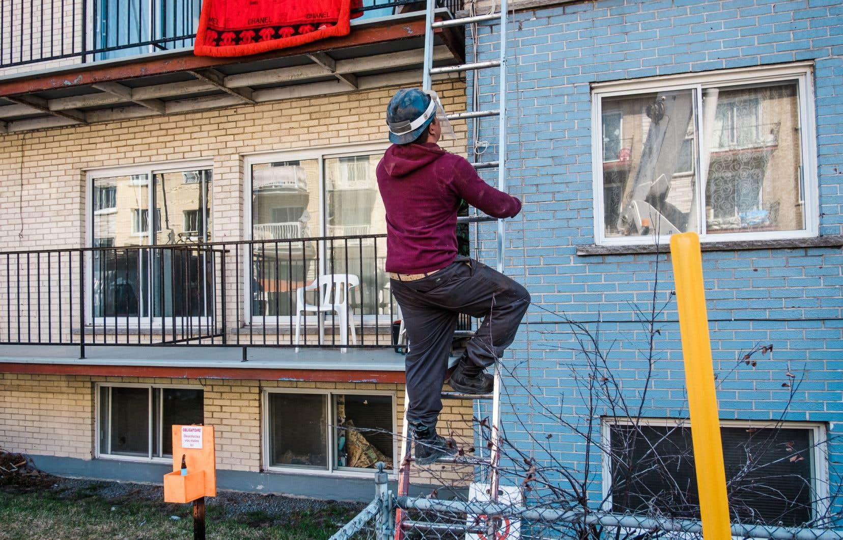 Des travailleurs de la construction résidentielle refond une toiture à Montreal. Le secteur de la construction a généré 58 000 emplois, durant la semaine du 10 au 16mai.