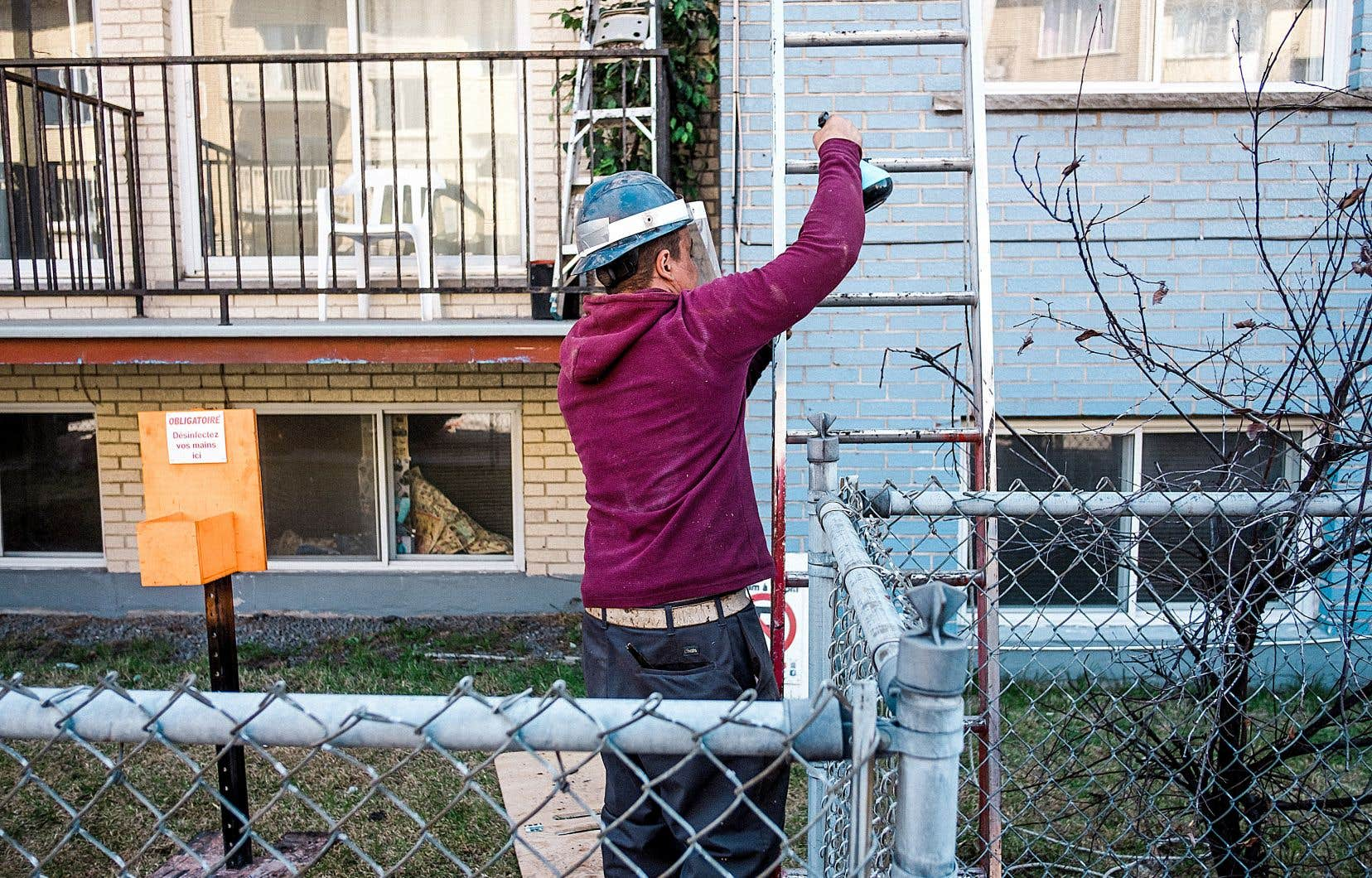 Un employé travaille à la réparation d'une toiture à Montréal.