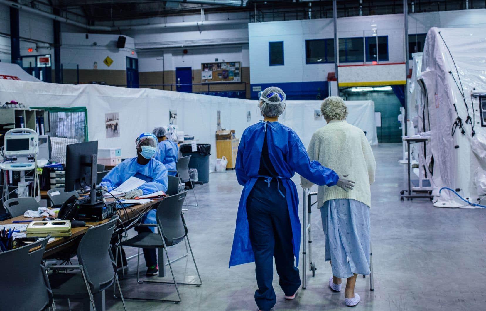 L'infirmière Marjorie Cosep accompagnait une patiente, Edythe Wilson, pendant sa marche quotidienne, fin mai, à l'intérieur de l'hôpital mobile de LaSalle.