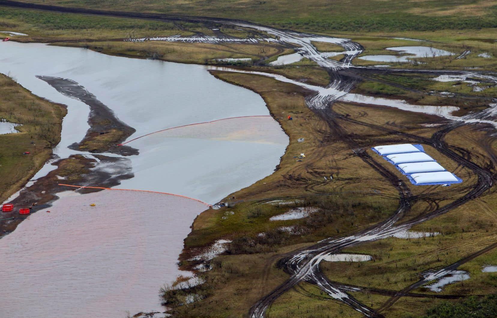 Les employés de Transneft ont mis dans la rivière des pompes pour aspirer l'eau souillée, colorée de rouge et retenue par des barrages flottants.