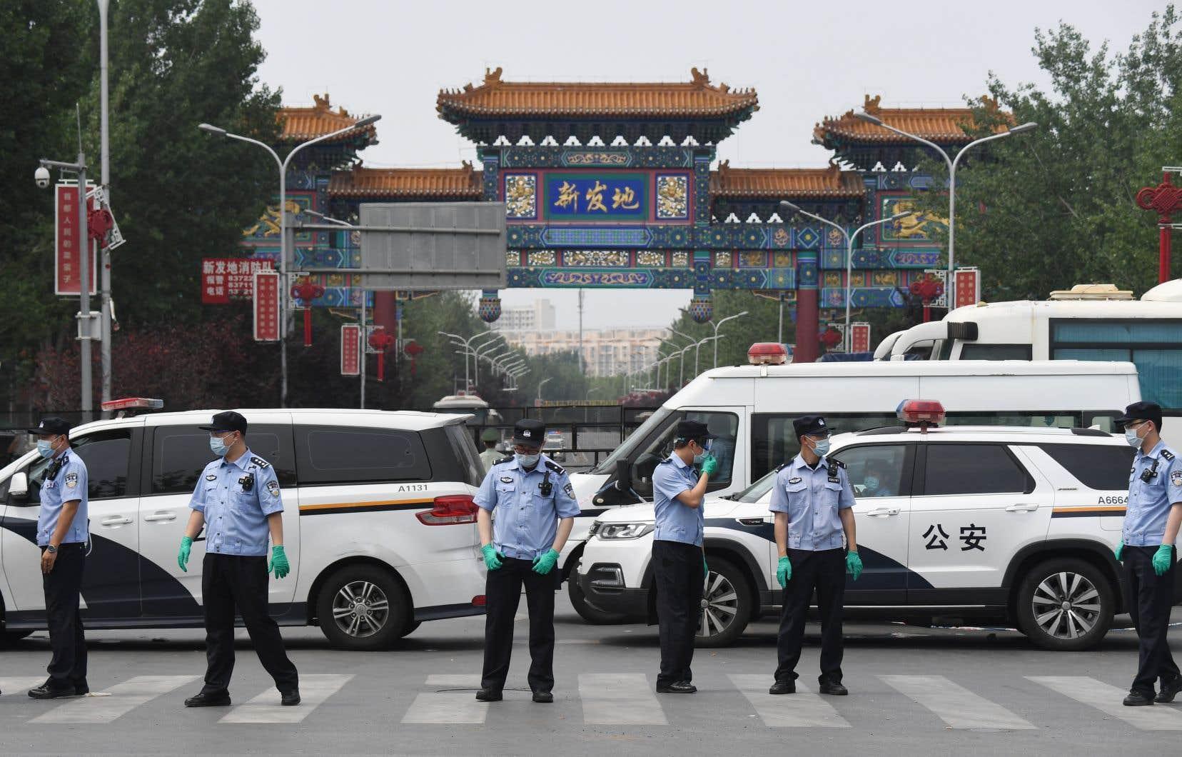 Les autorités chinoises ont signalé 49 nouveaux cas confirmés de COVID-19 en 24heures, dont 36 liés à un marché de gros à Pékin. Sur la photo, des policiers bloquant l'accès au marché Xinfadi.